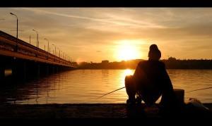 Рыболов на рыбалке на закате