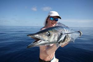 Мужчина в поляризационных очках держит рыбу
