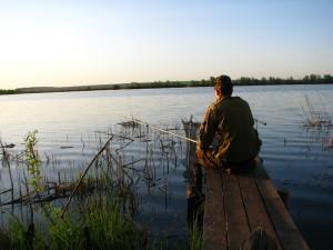Мужчина рыбачит на озере