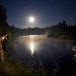 Мужчина рыбачит ночью