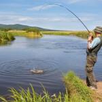 Мужчина ловит рыбу на пруду в Раково